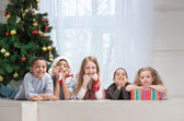 Smiling Children holding Christmas gifts — Stock Photo