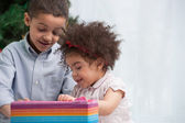 Brother and sister holding Christmas gifts — Stock Photo