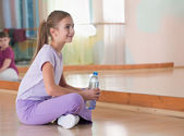 Girl in sportswear with bottle of water sits on the field at the gym in the — Stock Photo