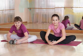 Two smiling girls engaged in physical training indoors. — Stock Photo