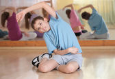 Boy and group of children engaged in physical training indoors. — Stock Photo