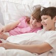 Children in bed playing game console. Close-up. — Stock Photo