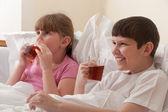 Irmão e irmã bebendo chá enquanto está sentado na cama. dentro de casa. close-up. — Foto Stock