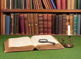 Antique leather books, tin candlestick and magnifying — Stock Photo
