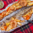 Stock Photo: Baked fish on tablecloth