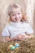 Laughing girl with sitting on the back of the Easter bunny — Stock Photo