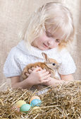 Little girl takes care of the Easter rabbit — Stock Photo