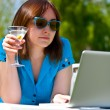 Businesswoman with laptop and glass of martini - Stock Photo