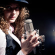 Royalty-Free Stock Photo: Beautiful singer in hat with microphone on the black background