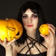 Woman with halloween makeup holding a pumpkin and an orange — Foto de Stock