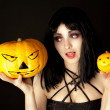 Woman with halloween makeup holding a pumpkin and an orange — Stock Photo