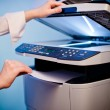 Woman's hand with working copier — Stock Photo
