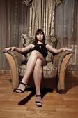 Sexy donna seduta in poltrona — Foto Stock