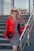 Woman in red jacket standing on the shop — Stock Photo