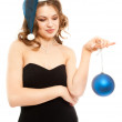 Beautiful woman in black dress smiling with blue new year ball — Stock Photo