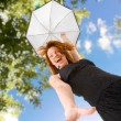 Happy red haired woman with umbrella outdoors — Stock Photo
