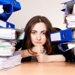 Frustrated businesswoman with stack of folders - Stock Photo