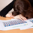 Stock Photo: Sleeping businesswomwith financial report