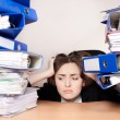 Frustrated businesswoman with stack of folders — Stock Photo