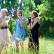 Picture of women smiling  and drinking in the forest - Stockfoto