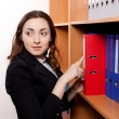 Woman taking a red folder from shelf — Stock Photo #16261625