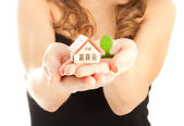 Woman's hands holding a house and a thee — Stock Photo
