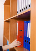 Woman's hand taking a red folder from shelf — Stock Photo