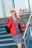 Beautiful woman in grey dress and red jacket — Стоковое фото