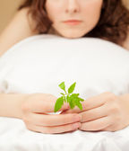 Vacker kvinna med en grön växt — Stockfoto