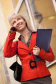 Businesswoman calling by phone outdoors — Stock Photo