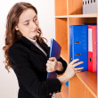 Woman taking a red folder from shelf — Stock Photo #18358861