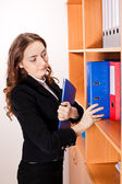 Woman taking a red folder from shelf — Stock Photo
