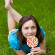 Beautiful woman with lollipop lying on the grass — Stock Photo #18786201