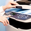 Stock Photo: Woman's hand with working copier