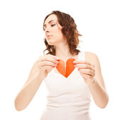 Attractive young girl holding broken paper red valentine heart — Stockfoto