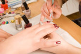 Woman with nail brush drawing on nails — Stock Photo