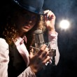 Beautiful singer in hat with microphone - Stok fotoğraf
