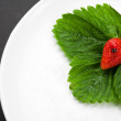 Strawberry with leaves on the white plate — Zdjęcie stockowe