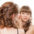 Woman looking to the mirror and putting earrings — Stock Photo #22581333