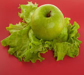 Picture of apple, lettuce on red background — Stock Photo