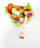 Picture of a plate with greek salad and tape- measure — Stock Photo