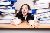 Gritos de mulher de negócios com a pilha de pastas no escritório — Fotografia Stock