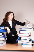 Frustrated businesswoman with stack of folders at office — Stock Photo