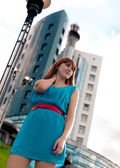 Beautiful woman in blue dress against building — Stock Photo