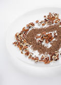 A plate with grated chocolate and sticks of cinnamons — Stock Photo