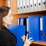 Woman taking a blue folder from shelf — Stock Photo #27454313