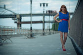 Beautiful woman in blue dress and red shoes — Stock Photo