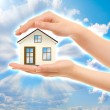 Picture of woman's hands holding a house against sky — Stockfoto