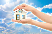Picture of woman's hands holding a house against sky — Stock Photo