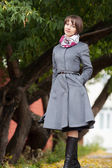 Foto van lachende jonge vrouw met grijze vacht — Stockfoto